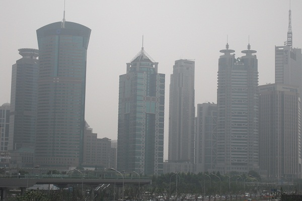 Le torri di banche e società finanziarie offuscate dalla coltre di smog svettano nel quartiere economico-finanziario di Shanghai.